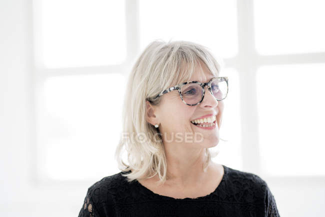 Laughing mature woman wearing glasses looking sideways — Stock Photo