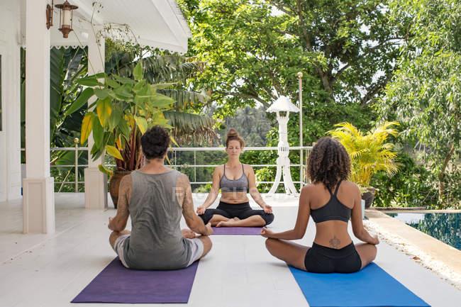 Zwei Frauen und ein Mann praktizieren Yoga am Pool — Stockfoto