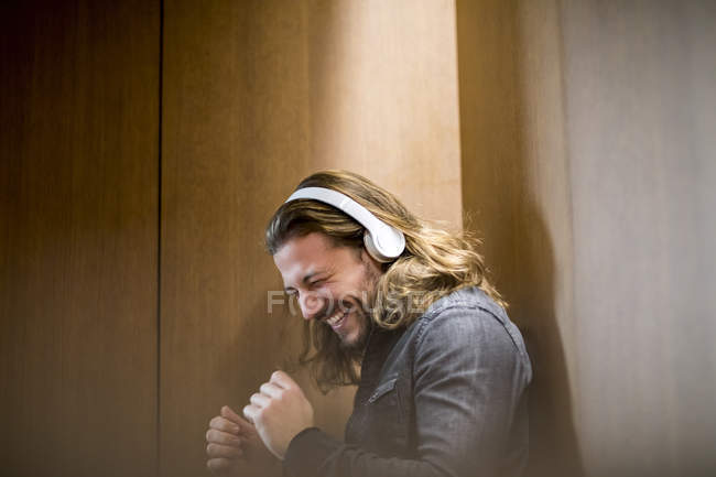 Portrait of excited man listening music with headphones — Stock Photo