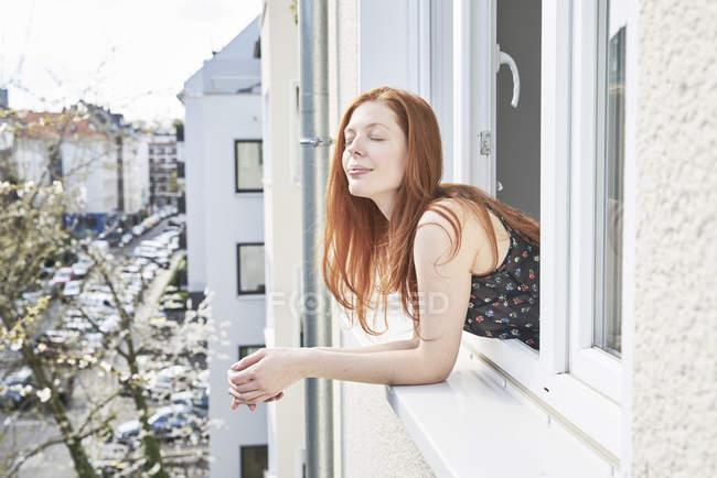 Retrato de mujer pelirroja con los ojos cerrados asomándose por la ventana - foto de stock