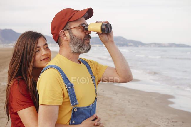 Casal com binóculos na praia — Fotografia de Stock
