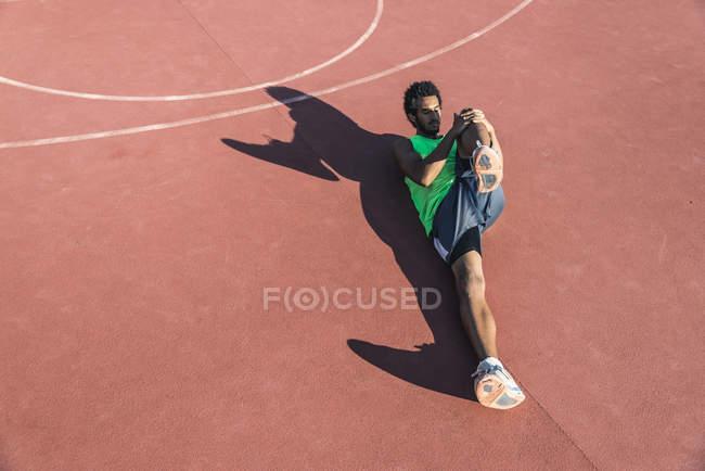 Молодой баскетболист растягивает ногу — стоковое фото