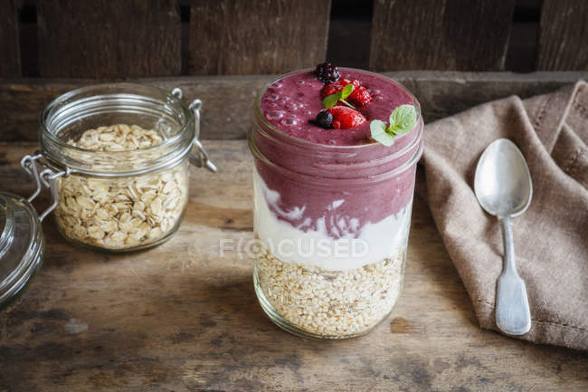 Vaso de batido berry, yogur natural y cereales - foto de stock