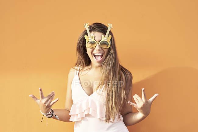 Портрет улыбающейся девушки в гитарных очках на фоне оранжевого фона — стоковое фото