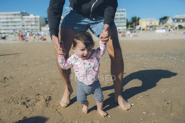 France, La Baule, baby girl learning to walk with her father on the beach — Stock Photo