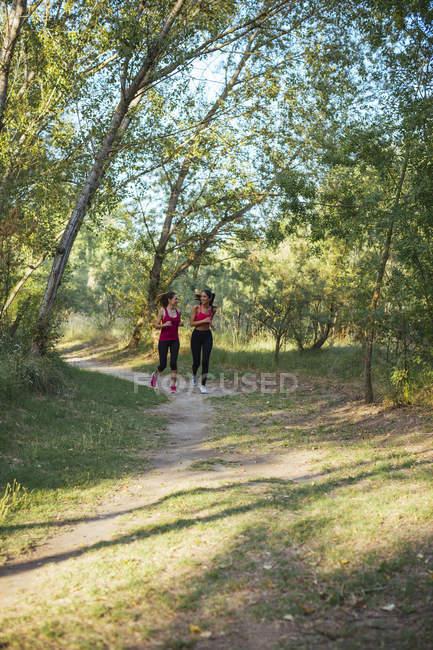 Duas mulheres ativas correndo na floresta — Fotografia de Stock