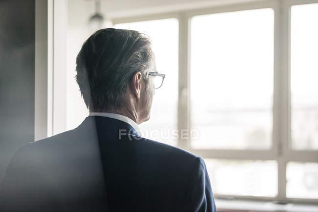 Задний вид зрелого бизнесмена, выглядывающего в окно — стоковое фото