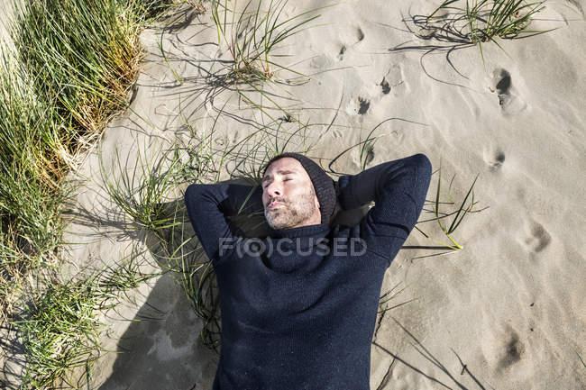 Man wearing woolly hat lying in beach dune — Stock Photo