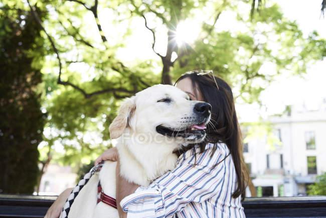 Jeune femme étreignant son chien — Photo de stock