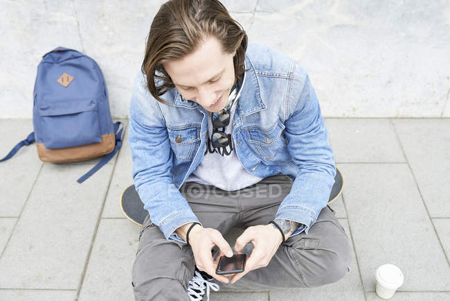 Young man with skateboard sitting on ground, using smartphone — Stock Photo