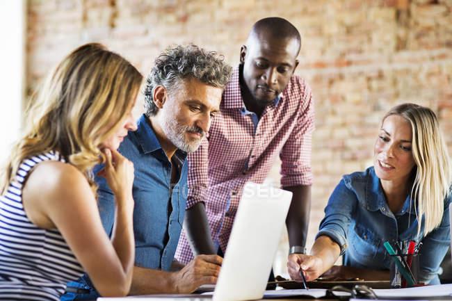 Деловые люди, работающие в офисе стартап-компании, имеющие встречу — стоковое фото