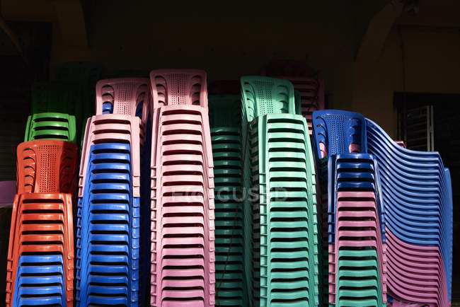 Stacks of coloured plastic chairs — Stock Photo