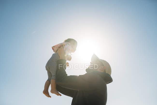Отец держит девочку на заднем плане — стоковое фото