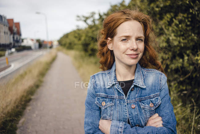 Redheaded woman with arms crossed, portrait — Stock Photo