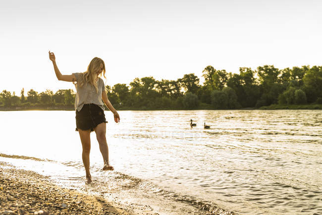 Young woman walking barefoot on riverside — Stock Photo