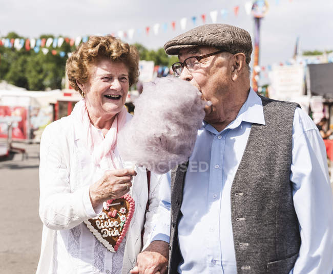 Casal sênior na feira desfrutando de algodão doce — Fotografia de Stock