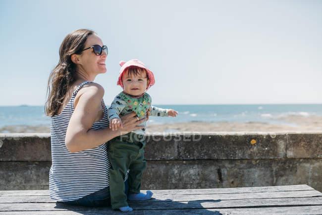 Francia, madre feliz y niña en un banco en el paseo marítimo - foto de stock