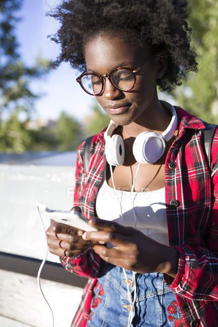 Retrato de mujer joven con auriculares usando teléfono celular - foto de stock