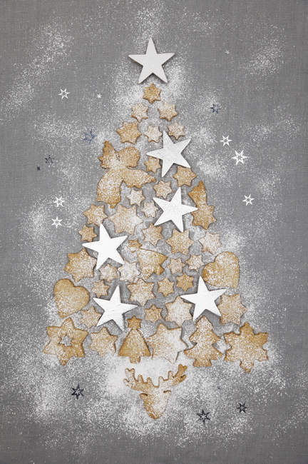 Christmas cookies and white stars forming Christmas Tree on grey background — Stock Photo