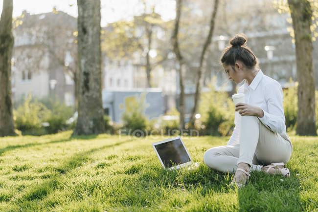 Молодая деловая женщина берет перерыв, используя ноутбук, сидя в траве и пить кофе — стоковое фото