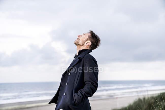 Entspannter Mann mit geschlossenen Augen am Strand — Stockfoto