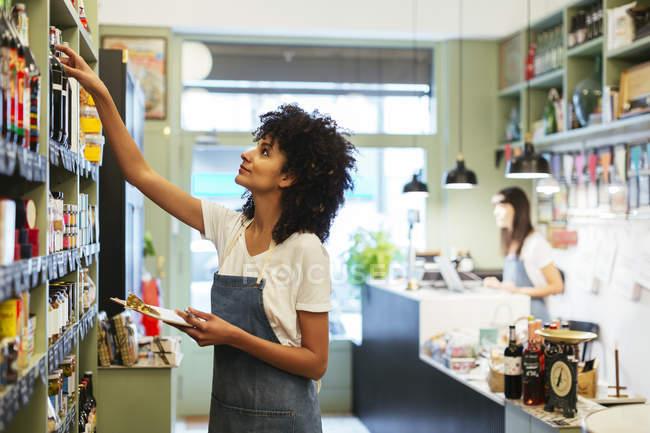 Женщина с планшетом на полке в магазине — стоковое фото