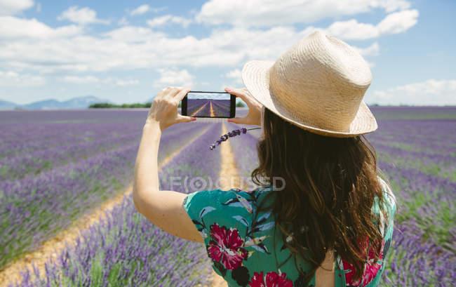 Francia, Provenza, donna in cappello scattare foto smartphone in campo lavanda in estate — Foto stock