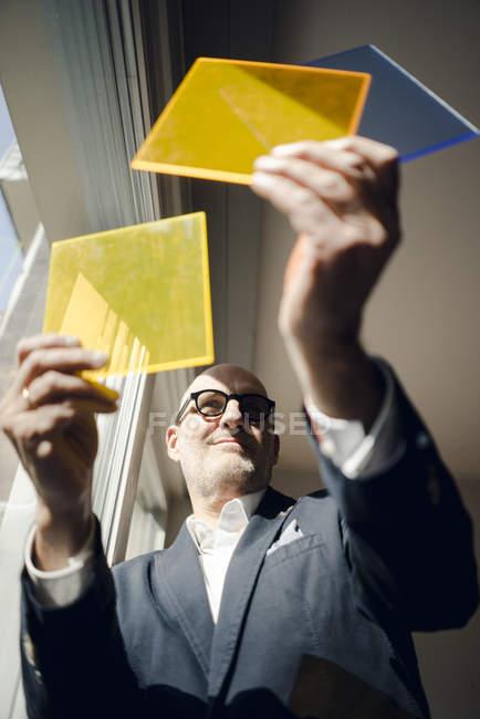 Senior architect standing at window, choosing materials — Stock Photo