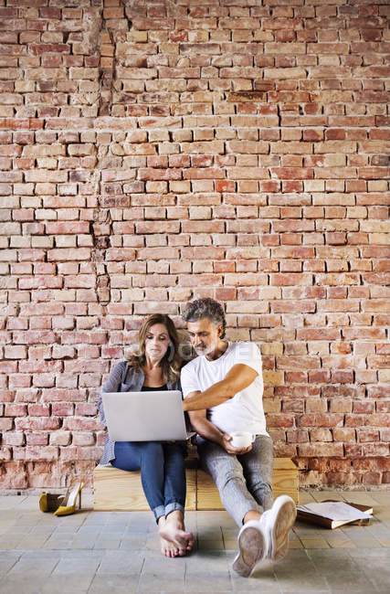 Businessman and woman sitting in a loft, using laptop, founding a start-up company — Stock Photo
