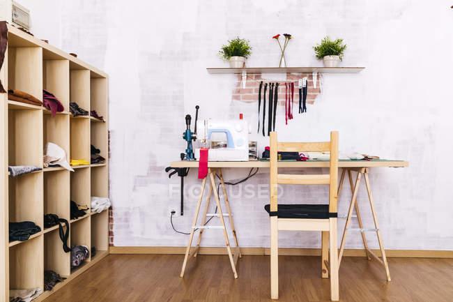 Spazio di lavoro con macchina da cucire sul tavolo in studio — Foto stock