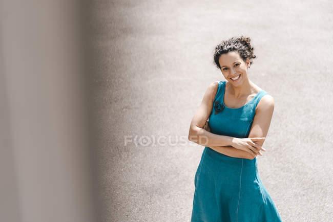 Lächelnde Frau, die mit verschränkten Armen im Hinterhof steht — Stockfoto