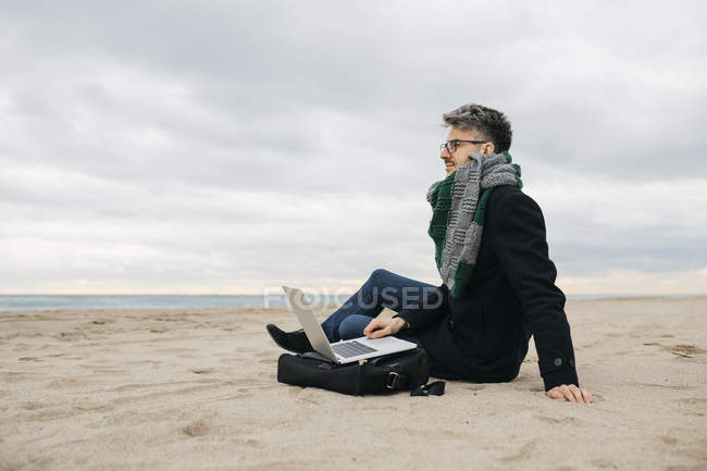 Businessman with laptop sitting on the beach in winter — Stock Photo