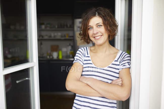 Reife Frau lehnt an geöffnete Balkontür — Stockfoto