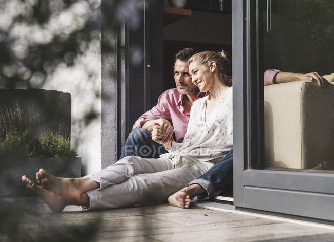 Content mature couple relaxing together at open terrace door — Stock Photo