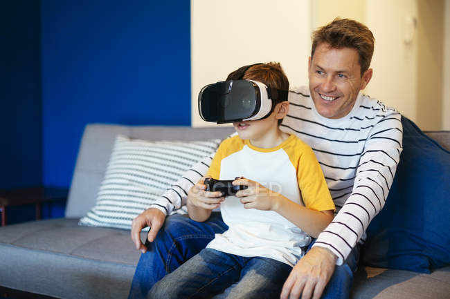 Boy wearing VR glasses playing video game with father on couch at home — Stock Photo
