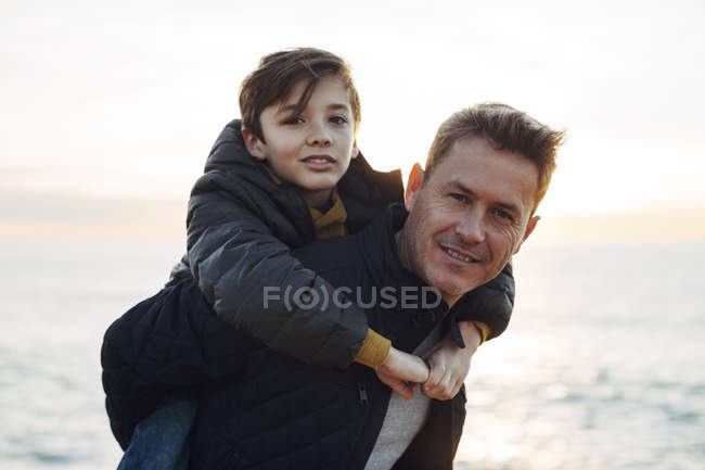 Father giving piggyback to son on beach at sunset — Stock Photo