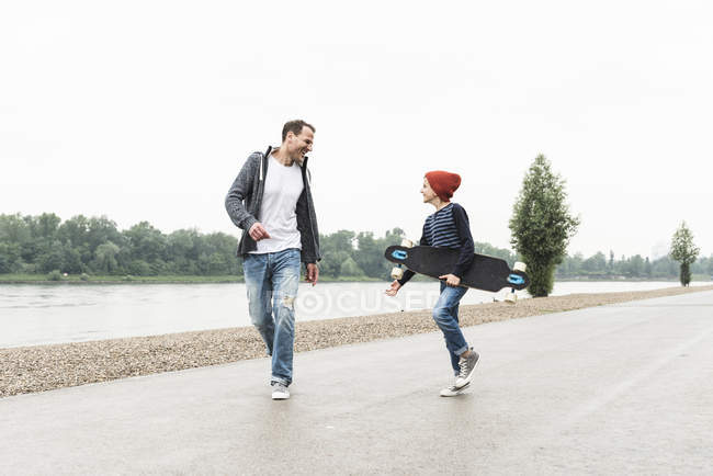 Happy father and son with skateboard at the riverside — Stock Photo
