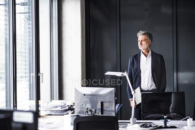Reifer Geschäftsmann steht im modernen Büro und schaut aus dem Fenster — Stockfoto