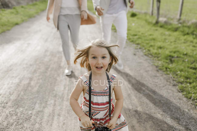 Portrait of excited little girl with camera — Stock Photo