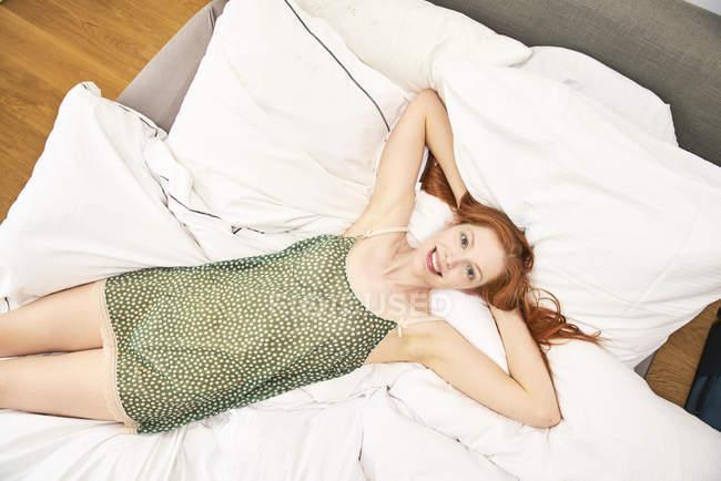 Retrato da mulher redheaded feliz que relaxa na cama — Fotografia de Stock