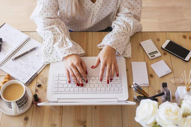 Молодая женщина сидит за столом, используя ноутбук — стоковое фото