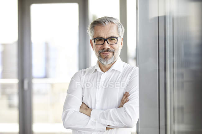 Retrato de um empresário sorridente em pé à janela — Fotografia de Stock
