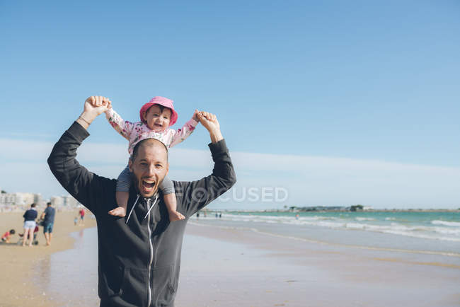 France, La Baule, portrait of father carrying his little daughter on shoulders on the beach — Stock Photo