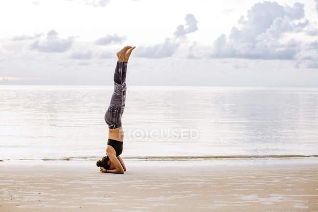 Таиланд, Ко Панган, Спортивная женщина, занимающаяся йогой на пляже — стоковое фото