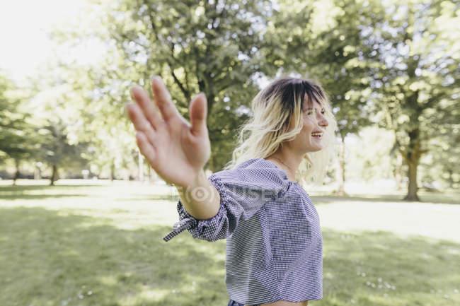 Joyeux jeune femme avec les bras tendus dans un parc — Photo de stock