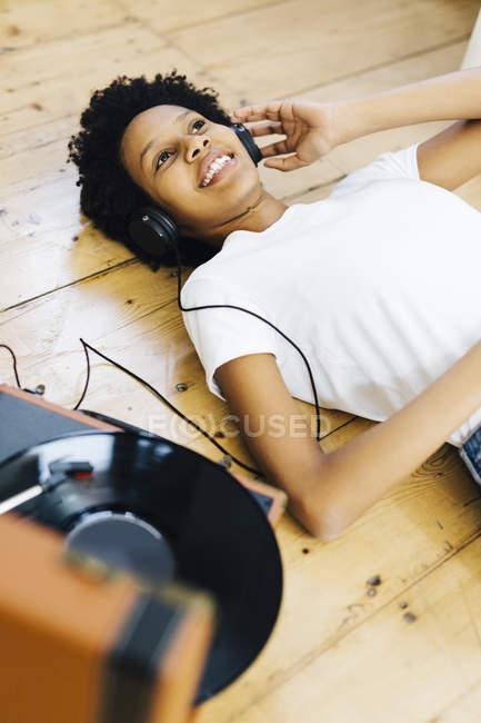Jeune femme afro-américaine à la maison écoutant des disques vinyles, allongée sur le sol — Photo de stock