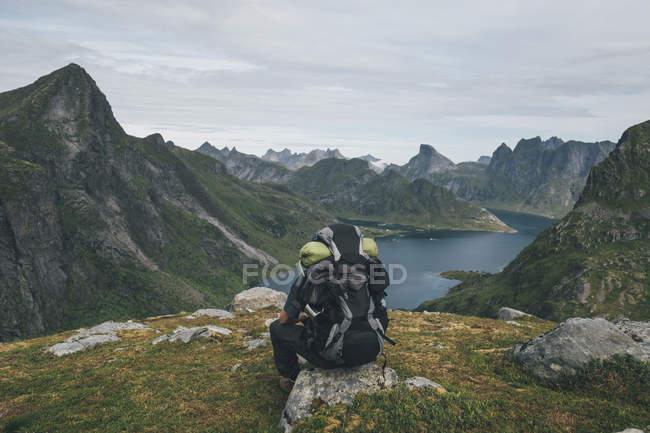 Норвегия, Лоффетт, Кенесой, Человек, сидящий на камне и смотрящий на Кьеркехорд — стоковое фото