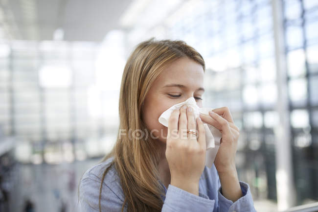 Young woman blowing nose — Stock Photo