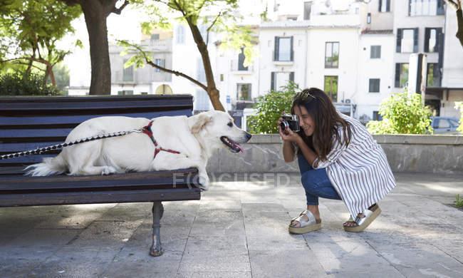 Giovane donna scattare foto del suo cane con fotocamera vintage — Foto stock