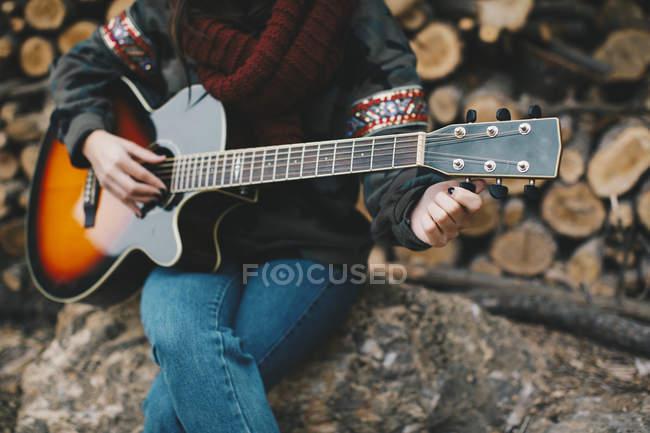 Молодая женщина настройка гитары на открытом воздухе, частичный вид — стоковое фото